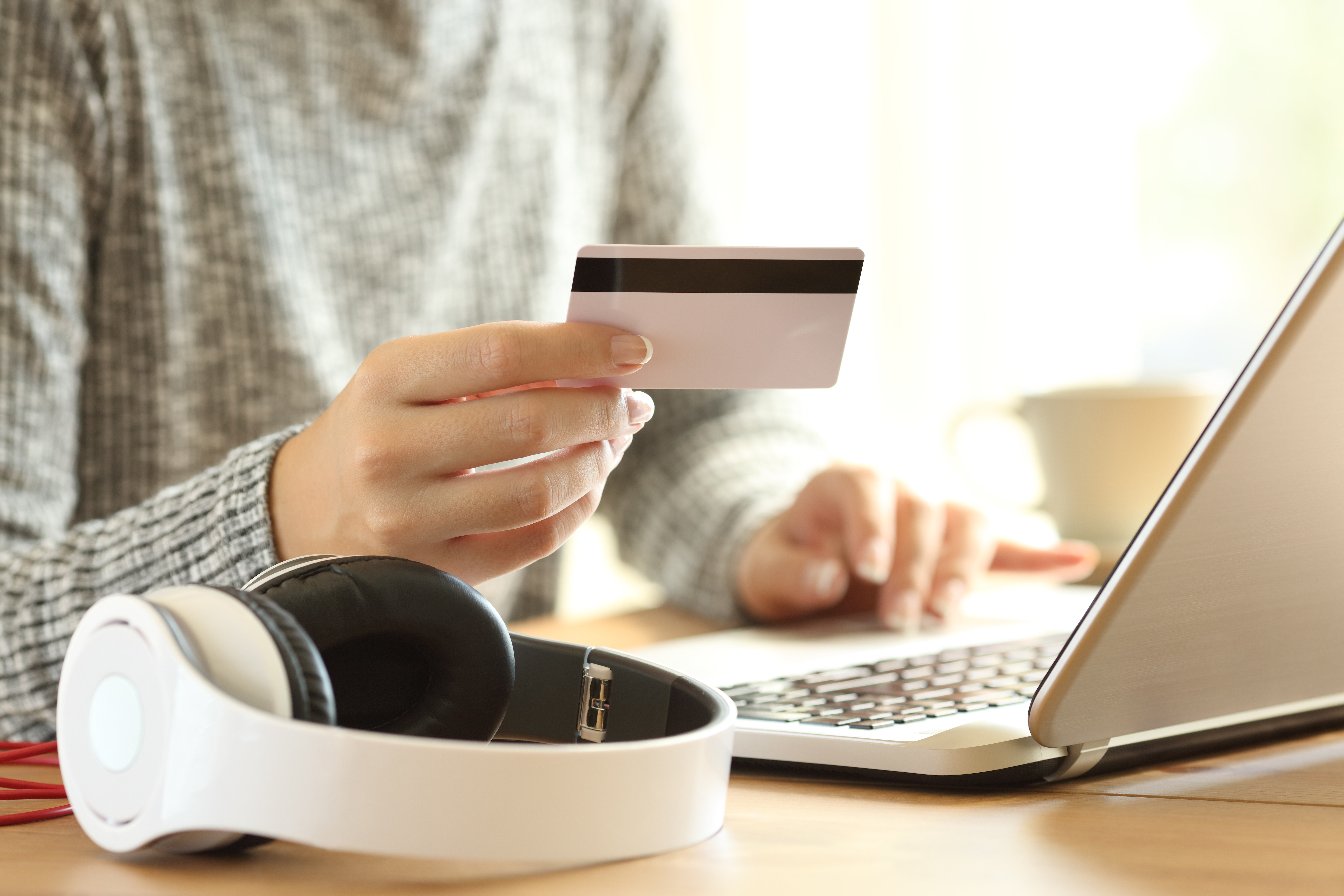 Woman making purchase on laptop with credit card next to headphones