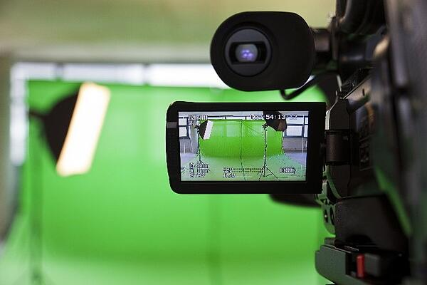 Video camera in front of a green screen