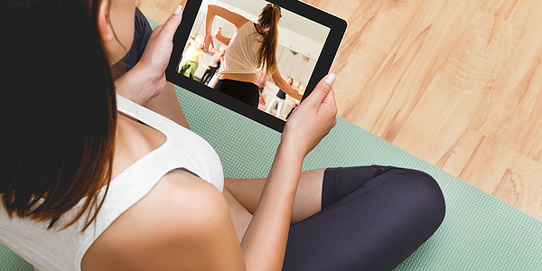 Woman watching a workout video on a tablet in workout clothes on a yoga mat.