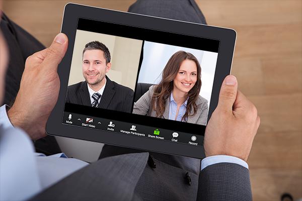 Man holding a tablet, having a meeting with coworkers on Zoom