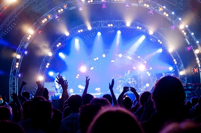 Music fans in front of lit up stage