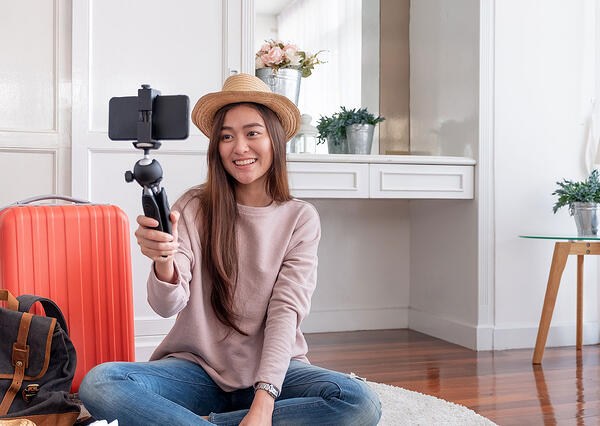 Asian woman with hat taking selfie next to luggage
