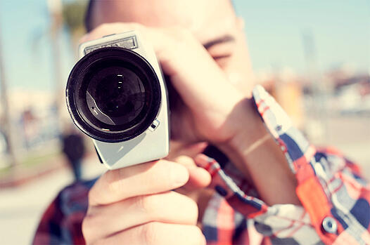 Man with video camera pointed at screen