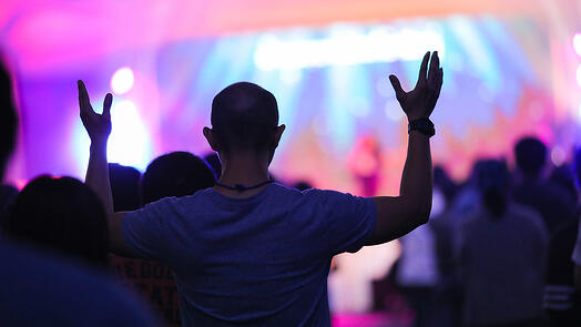Man with arms raised in a church worship service.